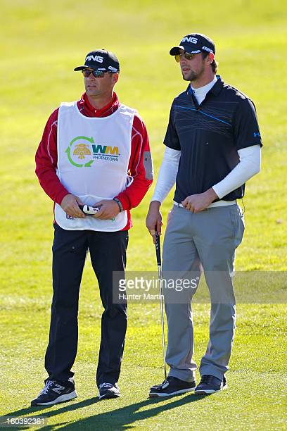 Michael Phelps stands with his caddie on the 18th green during the Wednesday ProAm of the Waste Management Phoenix Open at TPC Scottsdale on January...