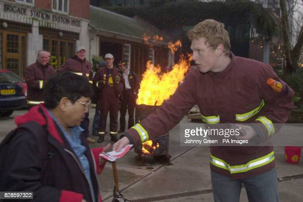 Michael Pole from Sunderland and a fire fighter at Euston Fire Station in central London gives out leaflets warning of what to do in case of fire as...