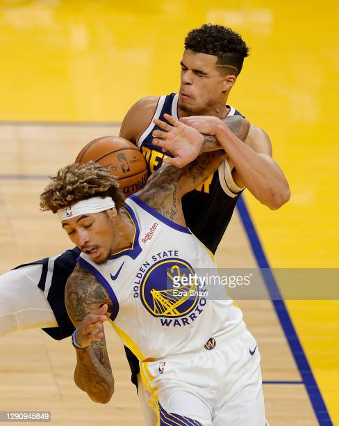 Michael Porter Jr. #1 of the Denver Nuggets and Kelly Oubre Jr. #12 of the Golden State Warriors go for a rebound during their NBA preseason game at...