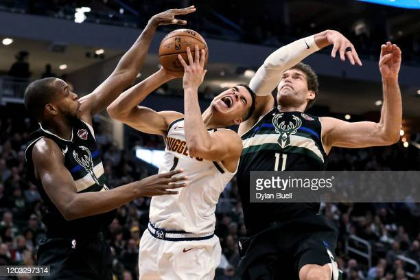 Michael Porter Jr #1 of the Denver Nuggets attempts a shot while being guarded by Khris Middleton and Brook Lopez of the Milwaukee Bucks in the third...