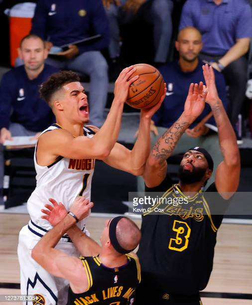 Michael Porter Jr #1 of the Denver Nuggets is charged with an offensive foul over Alex Caruso of the Los Angeles Lakers as Anthony Davis of the Los...