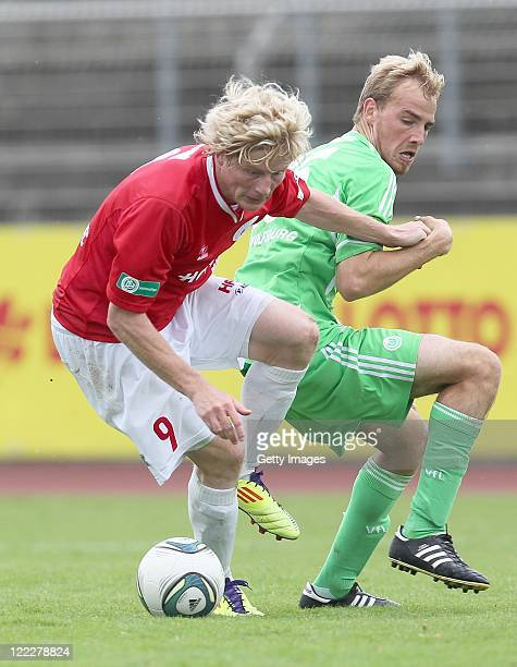 Michael Preuss of Halle and Rico Schlimpert of Wolfsburg fight for the ball during the Regionalliga North match between VfL Wolfsburg II and...