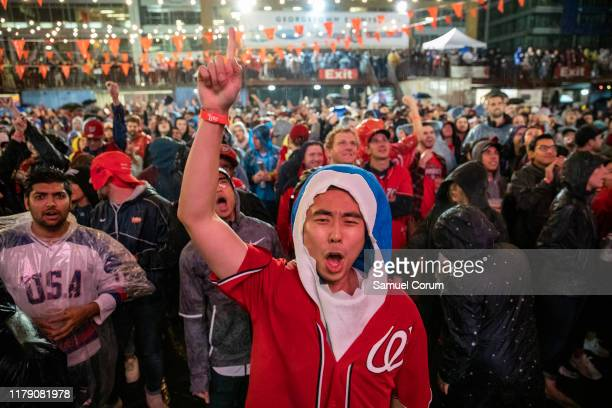 Michael Qu from Northern Virginia wearing a Baby Shark costume reacts to the World Series Game 7 on a big screen with other fans in the rain just a...