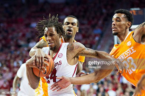 Michael Qualls of the Arkansas Razorbacks drives to the basket and is fouled by Kevin Punter and Derek Reese of the Tennessee Volunteers at Bud...