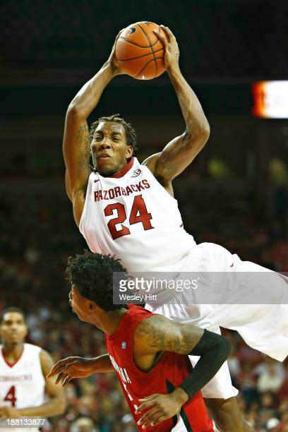 Michael Qualls of the Arkansas Razorbacks goes up for a rebound over the back of Elfrid Payton of the Louisiana Ragin' Cajuns at Bud Walton Arena on...