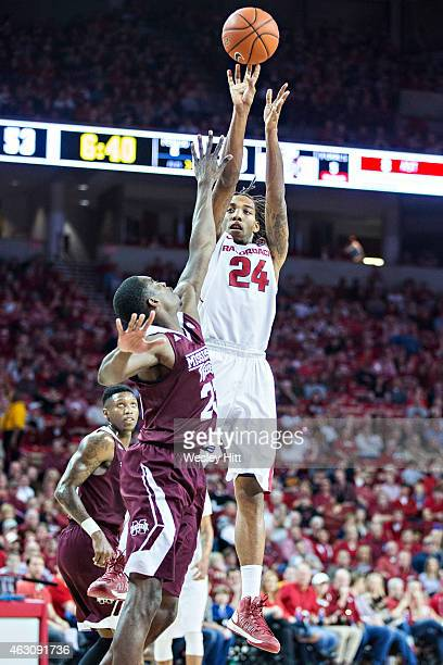 Michael Qualls of the Arkansas Razorbacks shoots a jump shot over Travis Daniels of the Mississippi State Bulldogs at Bud Walton Arena on February 7...