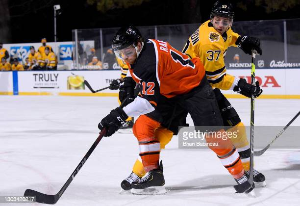 Michael Raffl of the Philadelphia Flyers and Patrice Bergeron of the Boston Bruins battle for the puck at center ice during the third period of the...