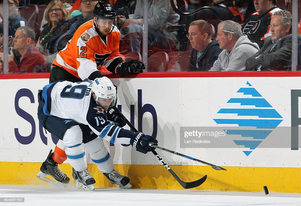 Michael Raffl #12 of the Philadelphia Flyers battles along the boards for the loose puck with Nic Petan #19 of the Winnipeg Jets on November 17, 2016 at the Wells Fargo Center in Philadelphia, Pennsylvania. The Flyers went on to defeat the Jets 5-2.
