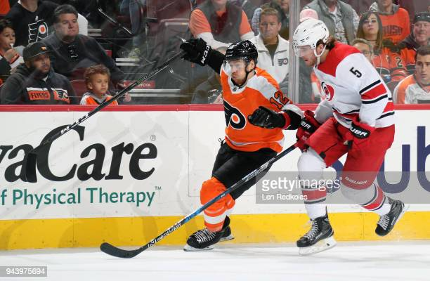 Michael Raffl of the Philadelphia Flyers battles along the boards against Noah Hanifin of the Carolina Hurricanes on April 5 2018 at the Wells Fargo...