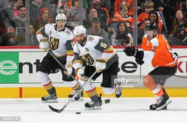 Michael Raffl of the Philadelphia Flyers battles for the puck against Deryk Engelland and Jon Merrill of the Vegas Golden Knights on March 12 2018 at...