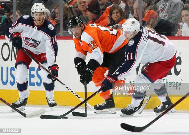Michael Raffl of the Philadelphia Flyers battles for the puck against Matt Calvert and Alexander Wennberg of the Columbus Blue Jackets on March 15...