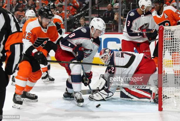 Michael Raffl of the Philadelphia Flyers battles for the puck in the crease against Zach Werenski and Sergei Bobrovsky of the Columbus Blue Jackets...