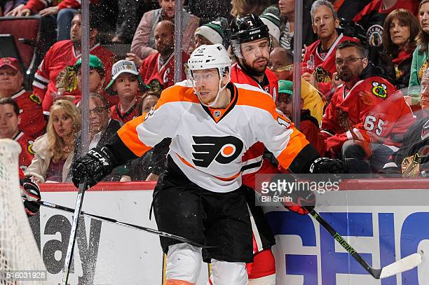 Michael Raffl of the Philadelphia Flyers checks Brent Seabrook of the Chicago Blackhawks into the boards in the first period of the NHL game at the...