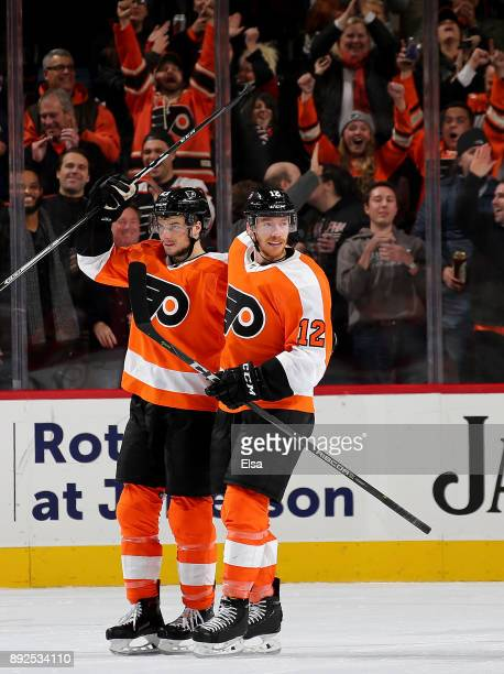 Michael Raffl of the Philadelphia Flyers congratulates teammate Scott Laughton after he scored an empty net goal in the third period against the...