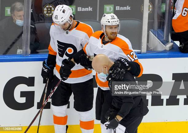 Michael Raffl of the Philadelphia Flyers has a few words as he is walked off the ice after a hit by Jeremy Lauzon of the Boston Bruins during Game...