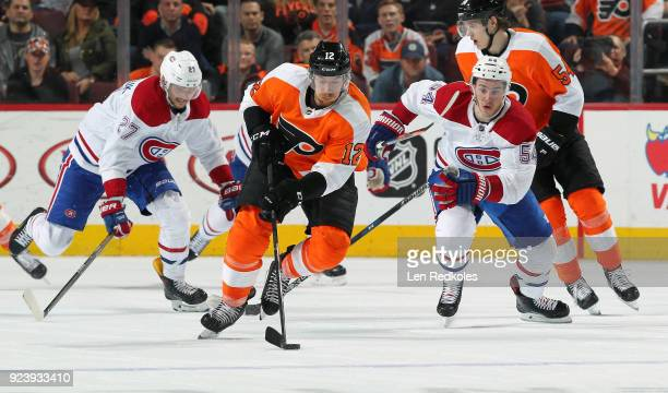 Michael Raffl of the Philadelphia Flyers skates the puck against Alex Galchenyuk and Charles Hudon of the Montreal Canadiens on February 20 2018 at...
