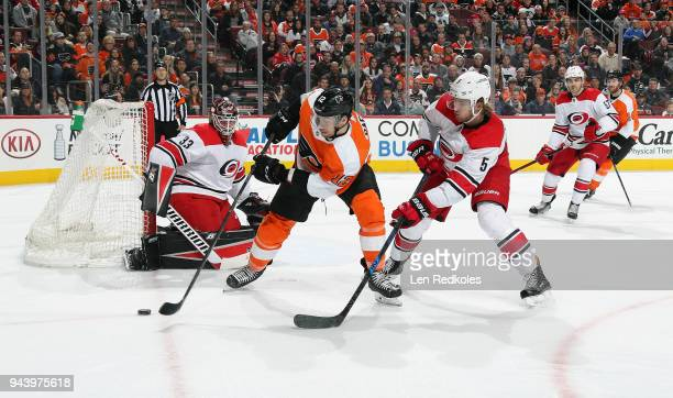 Michael Raffl of the Philadelphia Flyers skates the puck on a scoring opportunity against Noah Hanifin and Scott Darling of the Carolina Hurricanes...