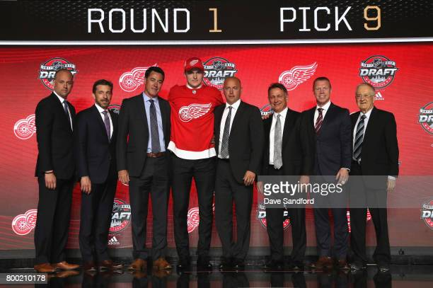 Michael Rasmussen ninth overall pick of the Detroit Red Wings poses onstage for a photo with the Red Wings draft team during Round One of the 2017...