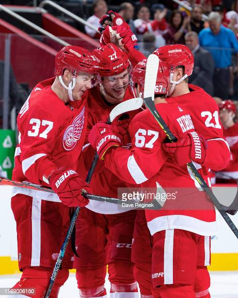 Michael Rasmussen of the Detroit Red Wings celebrates a goal with teammates against the Chicago Blackhawks during a pre-season NHL game at Little...
