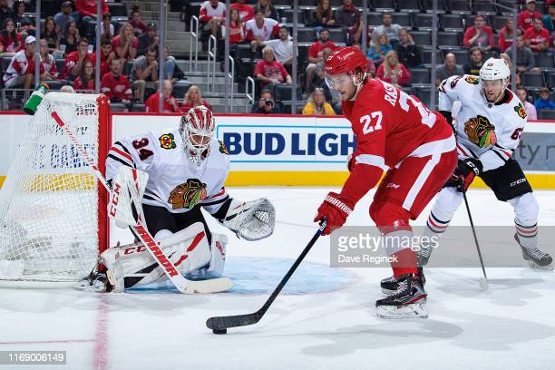 Michael Rasmussen of the Detroit Red Wings controls the puck between Kevin Lankinen and Carl Dahlstrom of the Chicago Blackhawks during a pre-season...