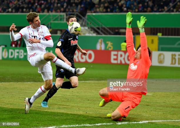 Michael Ratajczak goalkeeper of Paderborn makes a safe on Thomas Mueller of Muenchen during the DFB Cup quarter final match between SC Paderborn and...