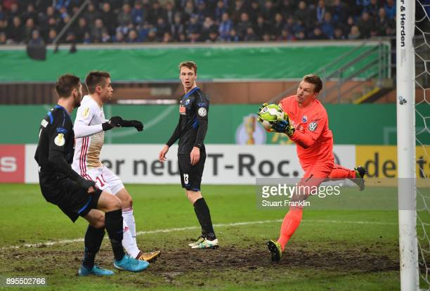 Michael Ratajczak of Paderborn makes a save from Stefan Lex of Ingolstadt during the DFB Cup match between SC Paderborn and FC Ingolstadt at Benteler...
