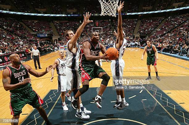 Michael Redd of the Milwaukee Bucks shoots against Nenad Krstic and Jason Collins of the New Jersey Nets on November 15 2006 at Continental Airlines...
