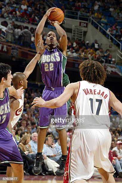Michael Redd of the Milwaukee Bucks shoots over Eric Snow and Anderson Varejao of the Cleveland Cavaliers at Gund Arena on April 9 2005 in Cleveland...