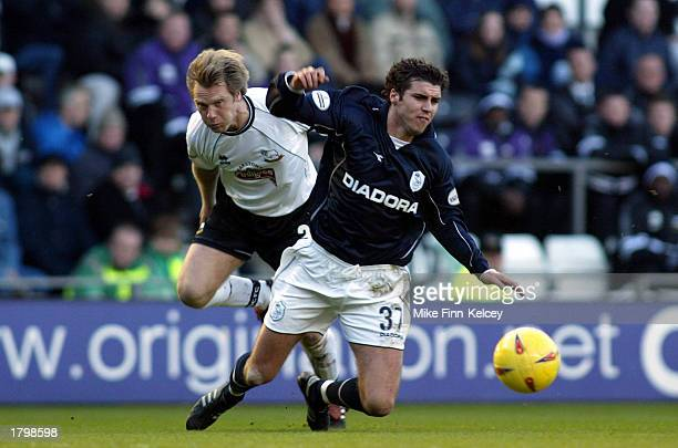 Michael Reddy of Sheffield Wednesday is fouled by Warren Barton of Derby County during the Nationwide League Division One League match between Derby...