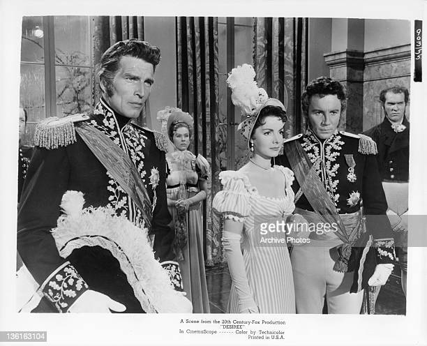 Michael Rennie stands near as Elizabeth Sellars holds the hand of unidentified actor in a scene from the film 'Desiree' 1954