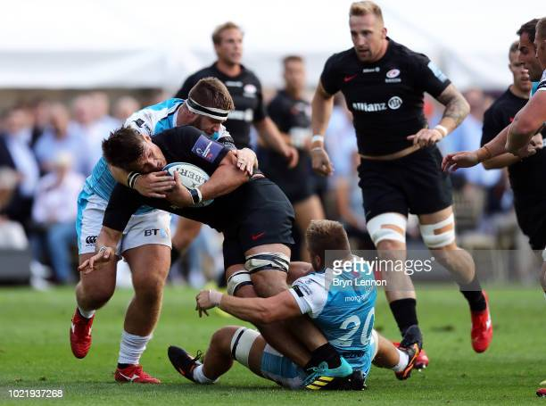 Michael Rhodes of Saracens is tackled by Ifan Phillips and Rhodri Jones of Ospreys during the preseason match between Saracens and Ospreys at the...