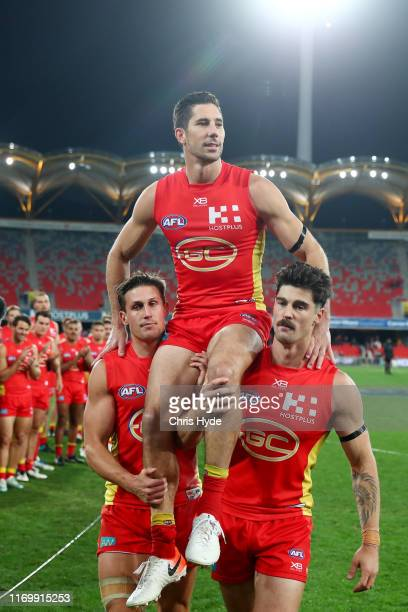 Michael Rischitelli of the Suns is chaired off after his last match during the round 23 AFL match between the Gold Coast Suns and the Greater Western...