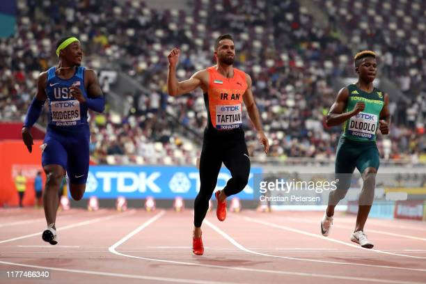 Michael Rodgers of the United States Hassan Taftian of Iran and Thando Dlodlo of South Africa compete in the Men's 100 metres heats during day one of...
