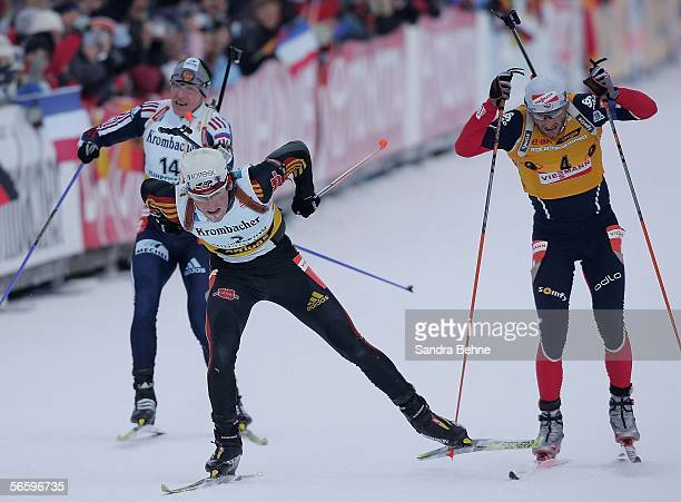 Michael Roesch of Germany crosses the finish line ahaed of Raphael Poiree of France and Sergei Tchepikov of Russia during the men's 12,5 km pursuit...