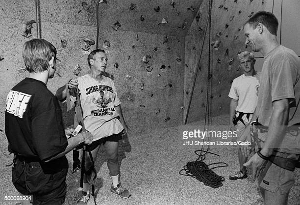 Michael Rubens Bloomberg Candid shot Bloomberg is standing in front of an indoor climbing wall and holding a climbing harness in his hand while...