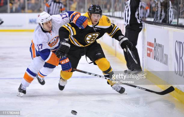 Michael Ryder of the Boston Bruins fights for the puck against Matt Martin of the New York Islanders at the TD Garden on April 6 2011 in Boston...