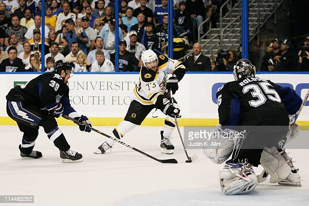 Michael Ryder of the Boston Bruins shoots a first period goal against the defense of Mike Lundin and Dwayne Roloson of the Tampa Bay Lightning in...