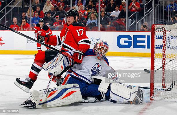 Michael Ryder of the New Jersey Devils falls onto Ilya Bryzgalov of the Edmonton Oilers during the second period at the Prudential Center on February...