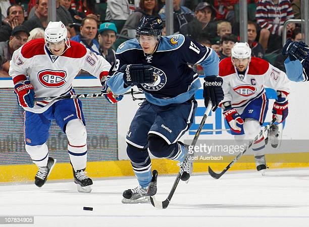 Michael Santorelli of the Florida Panthers skates the puck through center ice while being pursued by Max Pacioretty of the Montreal Canadiens on...