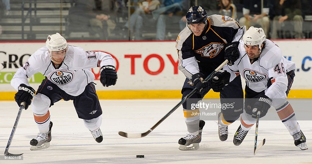Michael Santorelli #18 of the Nashville Predators battles for the puck against Zack Stortini #46 and Andrew Cogliano #13 of the Edmonton Oilers on October 12, 2009 at the Sommet Center in Nashville, Tennessee.
