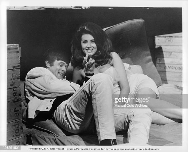 Michael Sarrazin smiling while laying down next to Gayle Hunnicutt in a scene from the film 'Eye Of The Cat' 1969