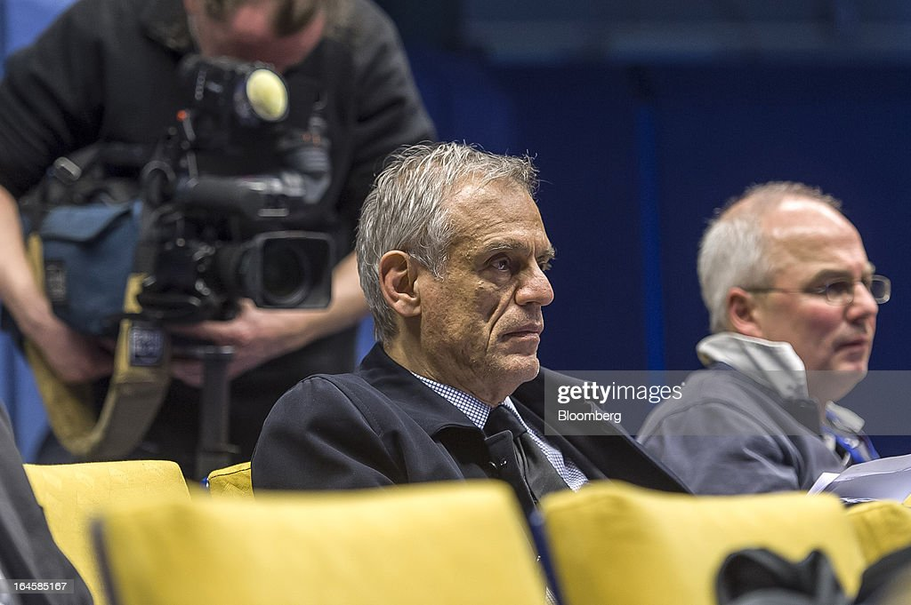Michael Sarris, Cyprus's finance minister, center, listens during a news conference following the Eurogroup meeting in Brussels, Belgium, on Monday, March 25, 2013. Cyprus dodged a disorderly default and unprecedented exit from the euro currency by bowing to demands to shrink its banking system in exchange for a 10 billion-euro ($13 billion) bailout. Photographer: Jock Fistick/Bloomberg via Getty Images