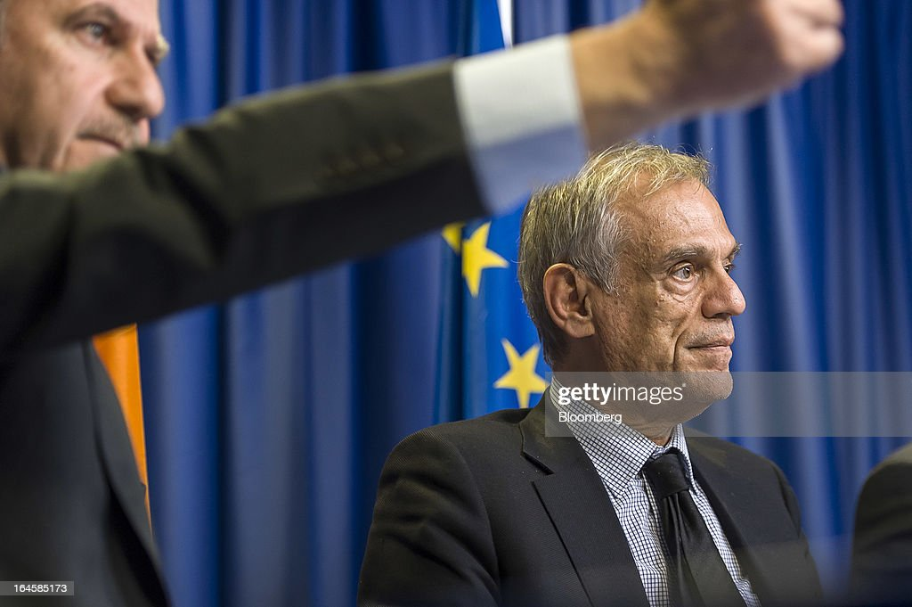 Michael Sarris, Cyprus's finance minister, right, attends a news conference following the Eurogroup meeting in Brussels, Belgium, on Monday, March 25, 2013. Cyprus dodged a disorderly default and unprecedented exit from the euro currency by bowing to demands to shrink its banking system in exchange for a 10 billion-euro ($13 billion) bailout. Photographer: Jock Fistick/Bloomberg via Getty Images