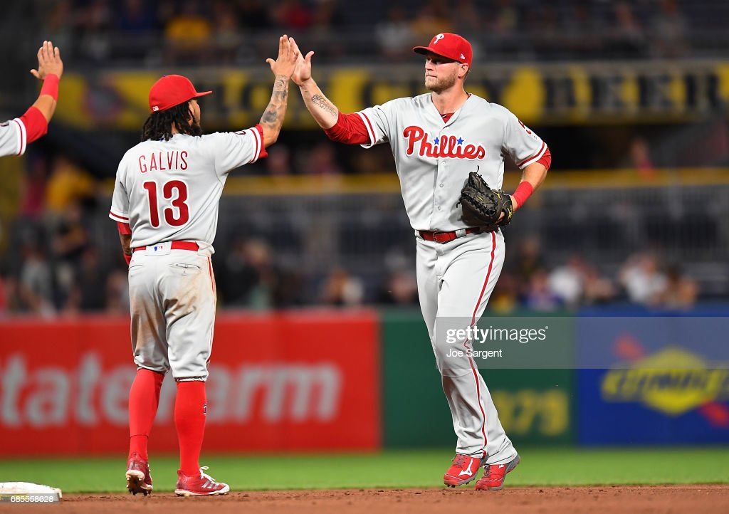 Michael Saunders #5 celebrates with Freddy Galvis #13 of the Philadelphia Phillies after a 7-2 win over the Pittsburgh Pirates at PNC Park on May 19, 2017 in Pittsburgh, Pennsylvania.