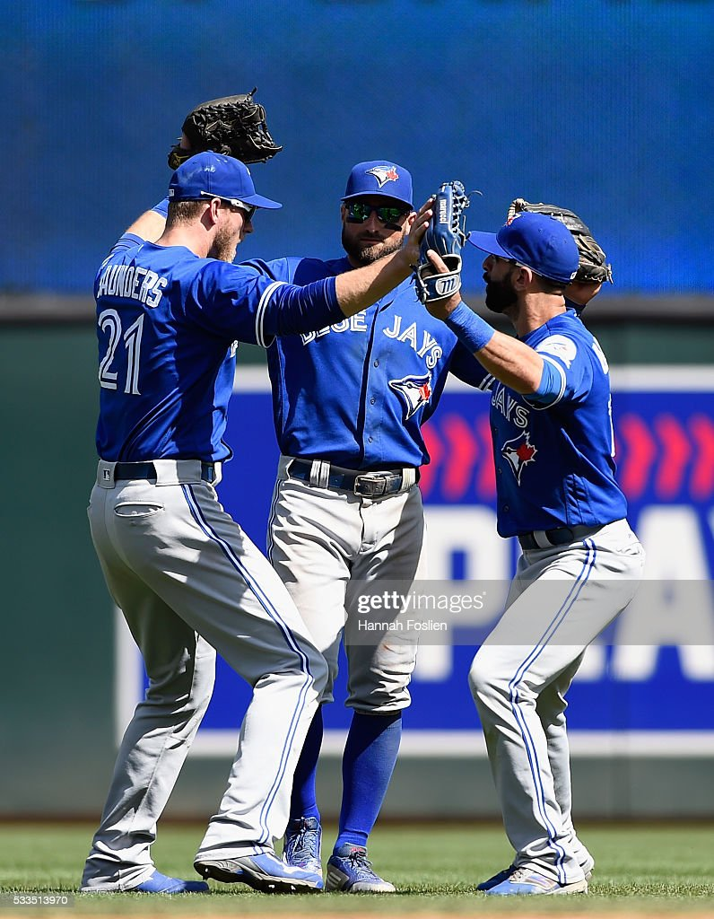 Michael Saunders #21, Kevin Pillar #11 and Jose Bautista #19 of the Toronto Blue Jays celebrate a win of the game against the Minnesota Twins on May 22, 2016 at Target Field in Minneapolis, Minnesota. The Blue Jays defeated the Twins 3-1.
