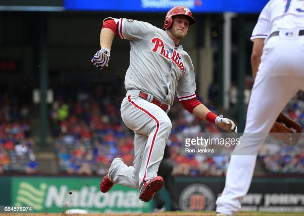Michael Saunders of the Philadelphia Phillies begins his slide into third base after hitting a triple against the Texas Rangers during the second...