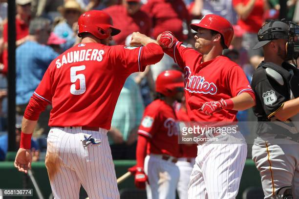 Michael Saunders of the Phillies congratulates Andrew Knapp after Knapp hit a home run during the spring training game between the Pittsburgh Pirates...