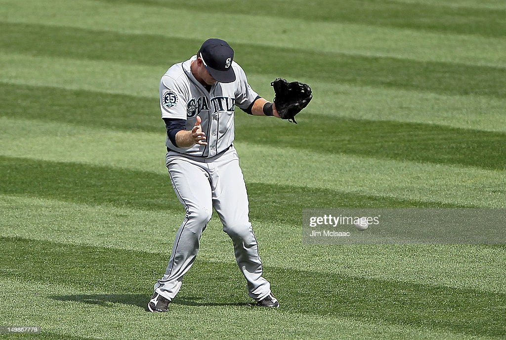 Michael Saunders #55 of the Seattle Mariners can't come up with a ball lost in the sun for a seventh inning double by Ichiro Suzuki #31 of the New York Yankees at Yankee Stadium on August 5, 2012 in the Bronx borough of New York City.