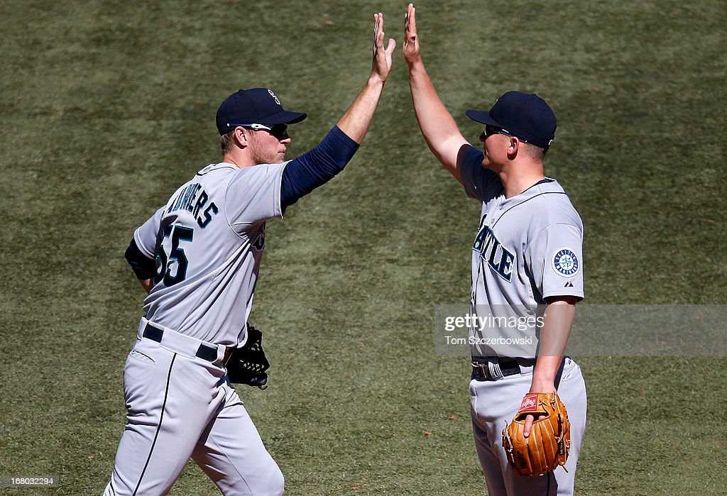 Michael Saunders #55 of the Seattle Mariners celebrates their victory with Kyle Seager #15 during MLB game action against the Toronto Blue Jays on May 4, 2013 at Rogers Centre in Toronto, Ontario, Canada.