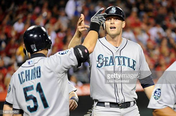 Michael Saunders of the Seattle Mariners celebrates with teammate Ichiro Suzuki after scoring in the fifth inning against the Los Angeles Angels of...
